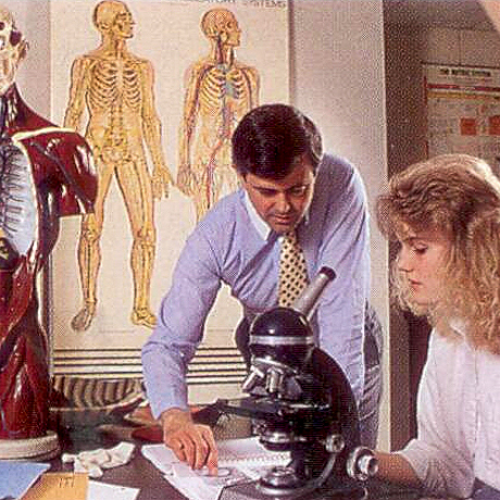 woman seated at microscope with professor leaning over, anatomical drawings in background