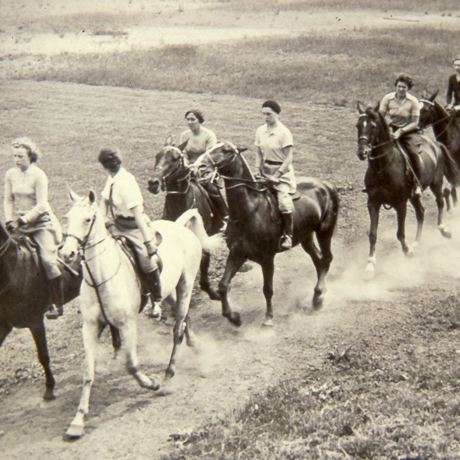 sepia image of women riding horses through field